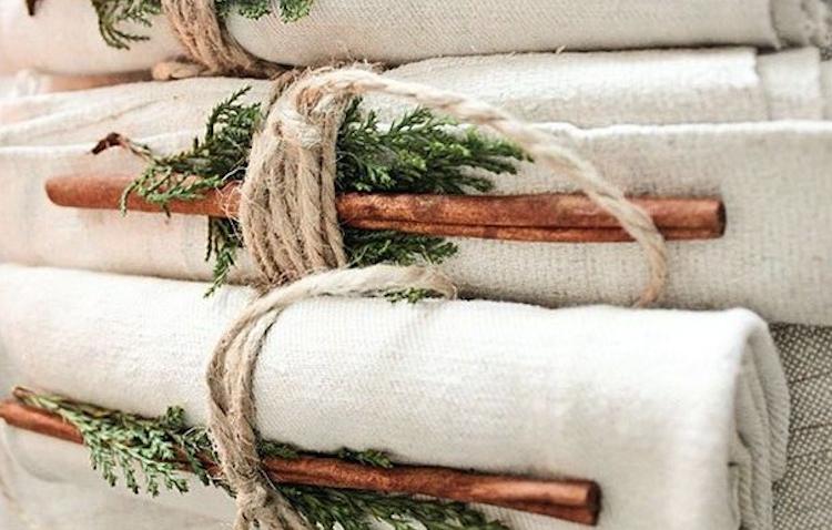 Еще один простой и эффектный способ украшения новогоднего стола: складываем тканевые салфетки, прикрепляем к каждой палочку корицы и еловую веточку, перевязываем получившуюся композицию бечевкой. Все готово!